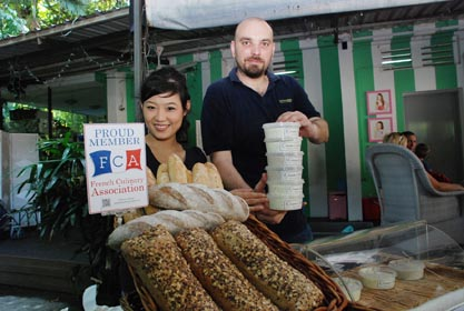 理查德(右)和任娟在市集里推销法籍名厨的佳肴。