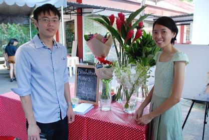 蓝振文(左)和蓝名姿摆摊售卖花卉,以了解外籍顾客对各种花类的需求。